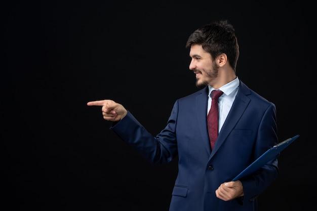 Tevreden mannelijke kantoormedewerker in pak die documenten vasthoudt en iets aan de rechterkant wijst op een geïsoleerde donkere muur