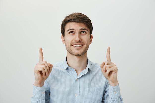 Tevreden mannelijke klant wijst en kijkt, glimlachend gelukkig