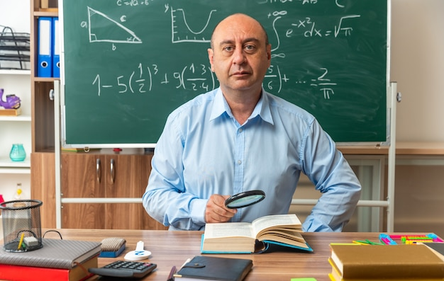 Tevreden mannelijke leraar van middelbare leeftijd zit aan tafel met schoolbenodigdheden met vergrootglas in de klas