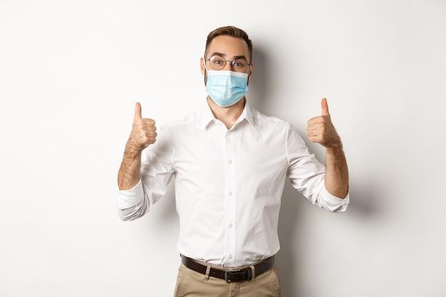 Tevreden mannelijke manager die duimen toont, adviseert om staand gezichtsmasker te dragen