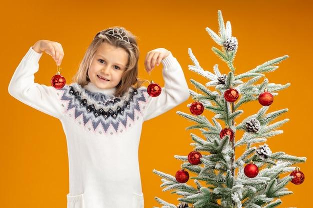 Tevreden meisje dat zich dichtbij kerstboom bevindt die tiara met slinger op hals draagt die kerstmisballen houdt die op oranje achtergrond worden geïsoleerd