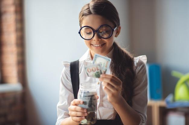 Tevreden. meisje in brillen geld steken in een pot en glimlachen