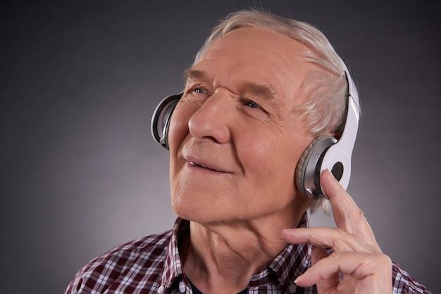 Tevreden mens die aan muziek op hoofdtelefoon luistert.