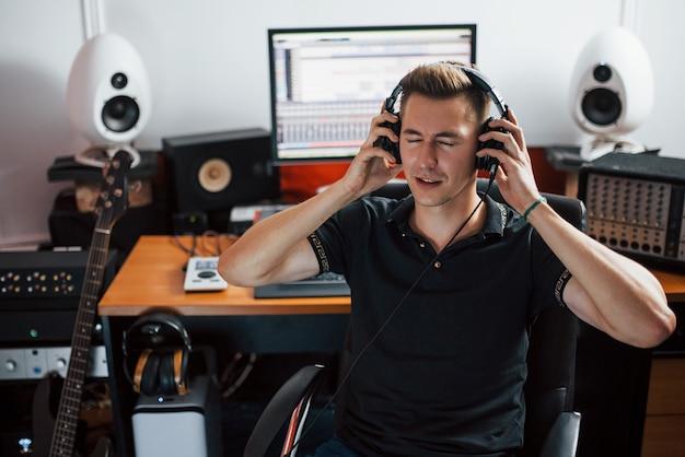 Tevreden met geluidskwaliteit. geluidstechnicus in koptelefoon die binnen in de studio werkt en muziek mixt.