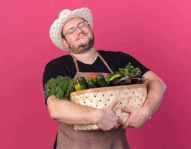 Tevreden met gesloten ogen jonge mannelijke tuinman die tuinierende hoed draagt die groentemand houdt die op roze muur wordt geïsoleerd