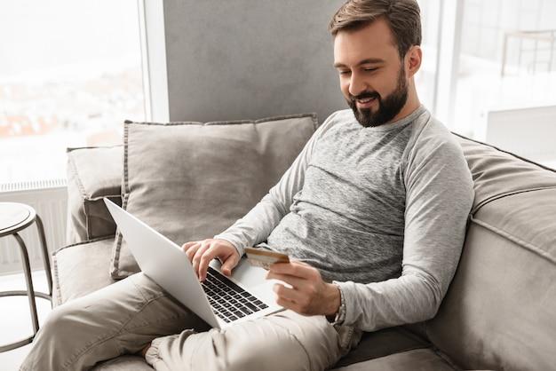 Tevreden moderne man jaren '30 in vrijetijdskleding zittend op de bank in de woonkamer, en het doen van betalingstransactie met creditcard en notebook