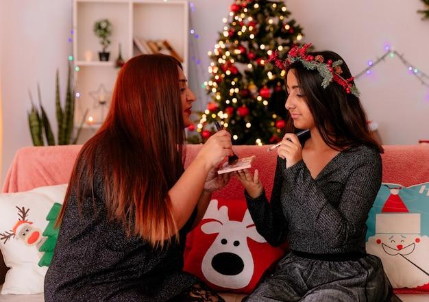 Tevreden moeder en dochter doen make-up zittend op de bank genieten van kersttijd thuis