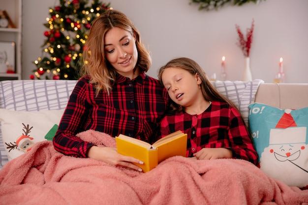 Tevreden moeder leest boek en vermoeide dochter slaapt bedekt met deken zittend op de bank en genieten van kersttijd thuis