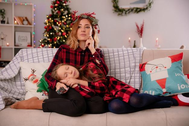 Tevreden moeder met holly krans houdt tv afstandsbediening en slaperige dochter liggend op haar schoot zittend op de bank en genieten van kersttijd thuis