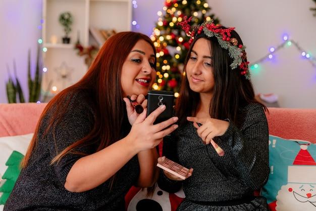 Tevreden moeder toont iets op de telefoon aan haar dochter zittend op de bank en geniet van kersttijd thuis