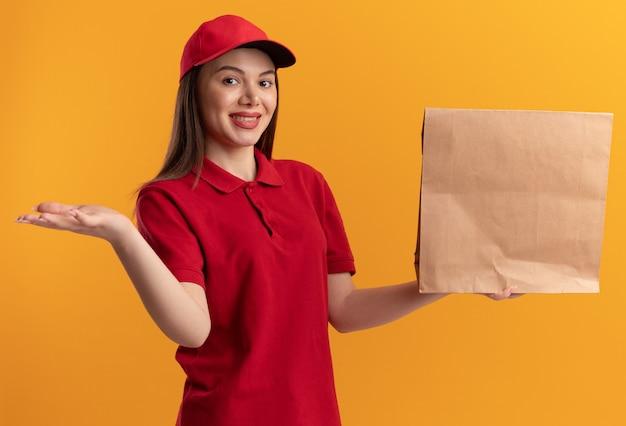 Tevreden mooie bezorger in uniform houdt de hand open en houdt het papieren pakket op oranje
