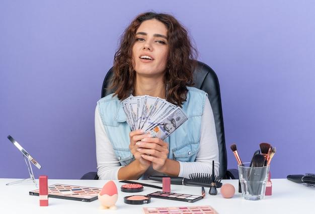 Tevreden mooie blanke vrouw die aan tafel zit met make-uptools die geld aanhouden