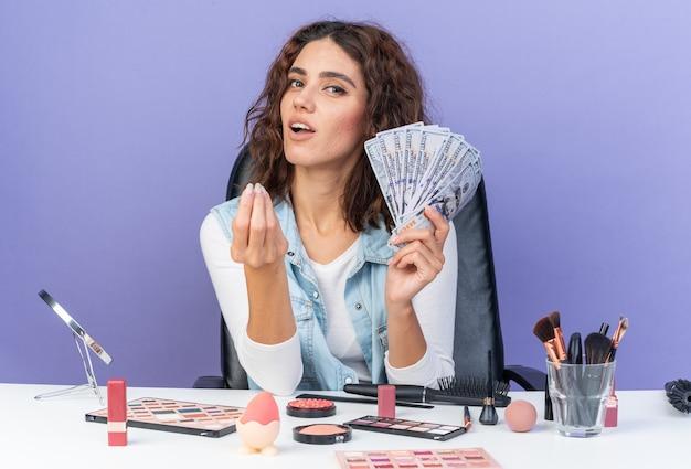 Tevreden, mooie blanke vrouw die aan tafel zit met make-uptools, houdt geld vast op een paarse muur met kopieerruimte