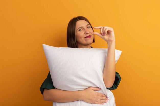Tevreden mooie blanke vrouw knuffelt kussen en doet alsof ze iets op sinaasappel vasthoudt