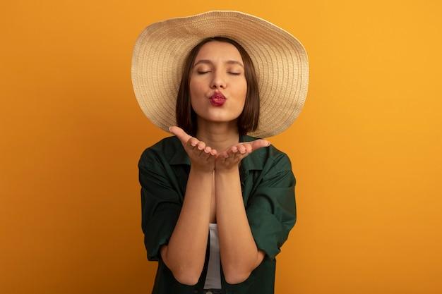 Tevreden mooie blanke vrouw met strandhoed stuurt kus met twee handen op sinaasappel