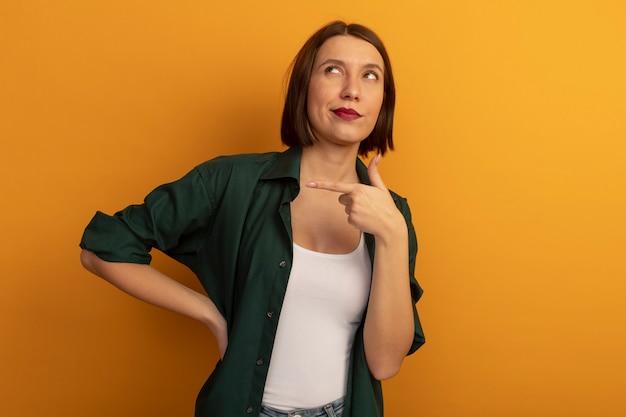 Tevreden mooie blanke vrouw wijst naar de zijkant op zoek op oranje