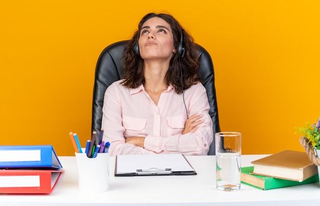 Tevreden, mooie blanke vrouwelijke callcenter-operator op een koptelefoon die aan het bureau zit met kantoorhulpmiddelen die de armen kruisen en omhoog kijken