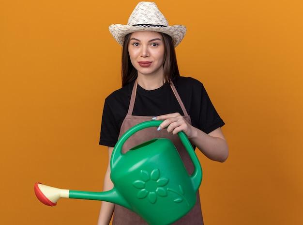 Tevreden mooie blanke vrouwelijke tuinman met een tuinhoed met een gieter geïsoleerd op een oranje muur met kopieerruimte