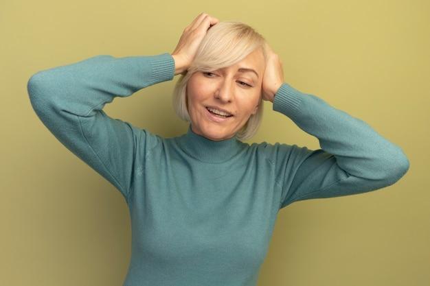 Tevreden mooie blonde slavische vrouw houdt het hoofd vast en kijkt naar de zijkant op olijfgroen