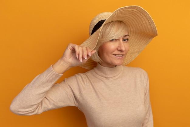Tevreden mooie blonde slavische vrouw met strandhoed houdt hoed op sinaasappel