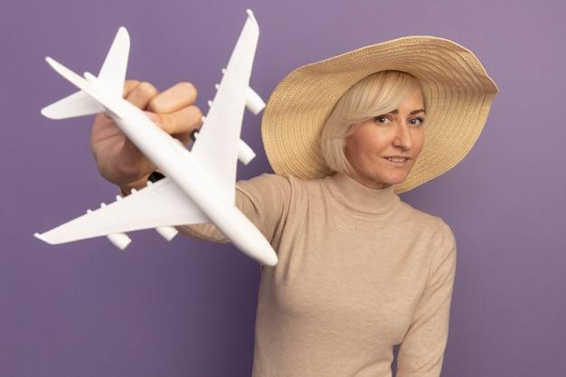 Tevreden mooie blonde slavische vrouw met strandhoed houdt modelvliegtuig op paars vast