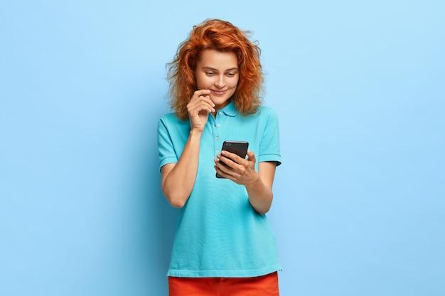Tevreden mooie gember vrouw houdt mobiele telefoon vast, blij om bericht te lezen met goed nieuws, draagt vrijetijdskleding, staat tegen blauwe muur, gebruikt graag moderne technologieën, heeft een zachte glimlach