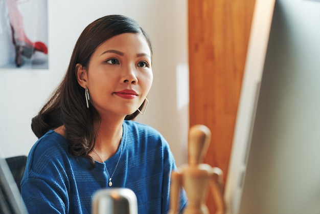 Tevreden mooie jonge aziatische creatieve ontwerper in oorbellen die in een modern kantoor zit en met de computer werkt