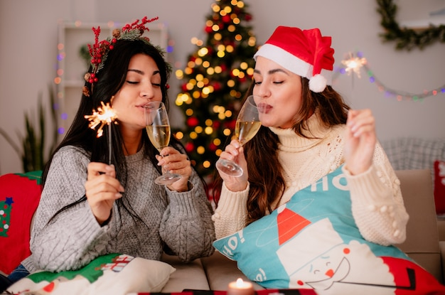 Tevreden mooie jonge meisjes met kerstmuts drinken glazen champagne en houden wonderkaarsen zittend op fauteuils en genieten van kersttijd thuis