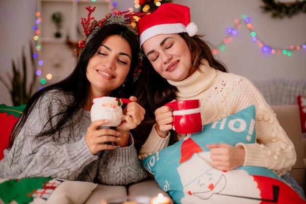 Tevreden mooie jonge meisjes met kerstmuts houden bekers zittend op fauteuils en genieten van kersttijd thuis
