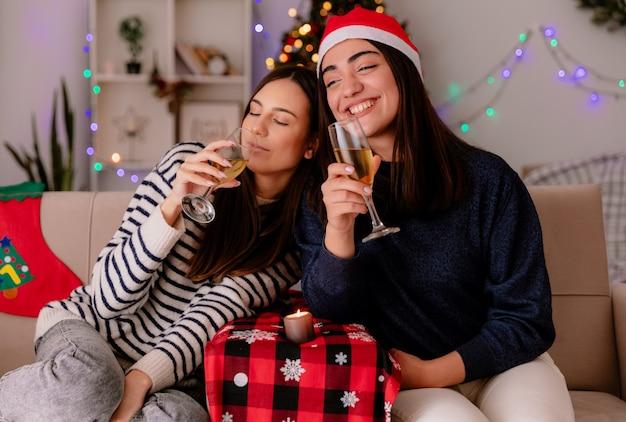 Tevreden mooie jonge meisjes met kerstmuts houden glazen champagne zittend op fauteuils en genieten van kersttijd thuis