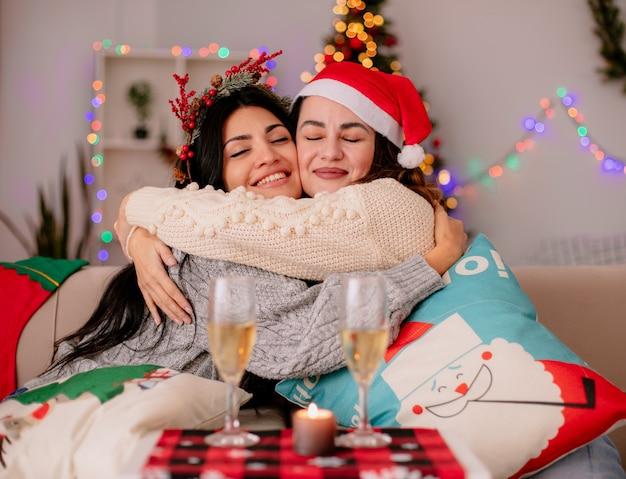 Tevreden mooie jonge meisjes met kerstmuts knuffelen elkaar zittend op fauteuils en genieten van kersttijd thuis