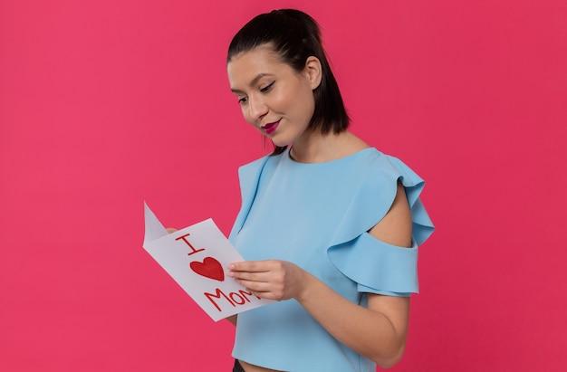 Tevreden mooie jonge vrouw die brief van haar kind leest