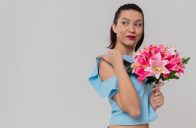 Tevreden mooie jonge vrouw die een boeket bloemen vasthoudt en naar de zijkant wijst