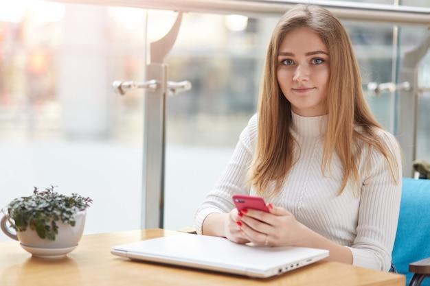 Tevreden mooie jonge vrouw in vrijetijdskleding gebruikt mobiele telefoon voor het verzenden van berichten, zit aan salontafel met gesloten laptop, mooie groene bloem in vaas, wacht op telefoontje van vriendje.