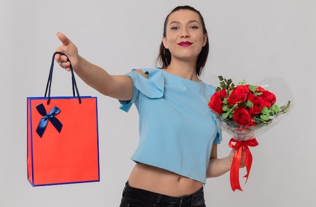 Tevreden mooie jonge vrouw met boeket bloemen en cadeauzakje kijkend naar de voorkant