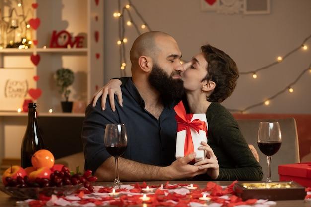 Tevreden mooie vrouw die een geschenkdoos geeft en een knappe man kust die op valentijnsdag aan tafel in de woonkamer zit