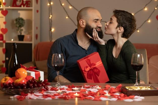 Tevreden mooie vrouw die een geschenkdoos vasthoudt en op valentijnsdag een knappe man probeert te kussen die aan tafel in de woonkamer zit