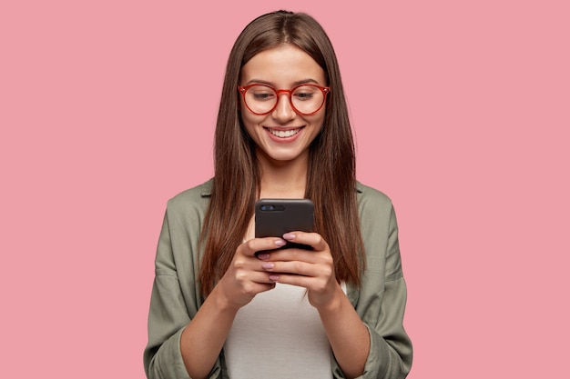 Tevreden mooie vrouw houdt moderne mobiele telefoon