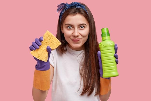 Tevreden mooie vrouw houdt schoonmaakset voor verschillende diensten, gekleed in een speciaal uniform
