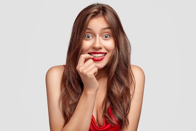 Tevreden mooie vrouw met donker haar, gezonde, zuivere huid, houdt de vinger dicht bij de tanden, heeft rood geverfde lippen, ziet er vrolijk uit, merkt iets prachtigs op, geïsoleerd over een witte muur.