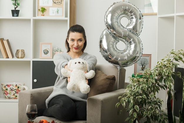 Tevreden mooie vrouw op gelukkige vrouwendag die teddybeer uithoudt bij camera zittend op fauteuil in woonkamer