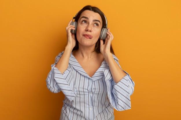 Tevreden mooie vrouw op koptelefoon steekt tong uit en kijkt omhoog geïsoleerd op oranje muur