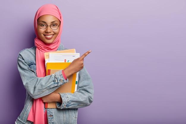 Tevreden moslimstudent met blocnote en papieren