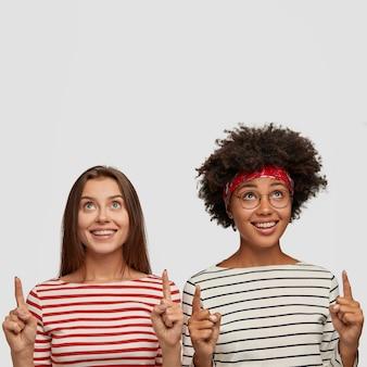 Tevreden onder de indruk vrouwen wijzen met beide wijsvingers, hebben blije uitdrukkingen, zien iets leuks, bespreken het met elkaar, staan tegen een witte muur, hebben plezier in goed gezelschap