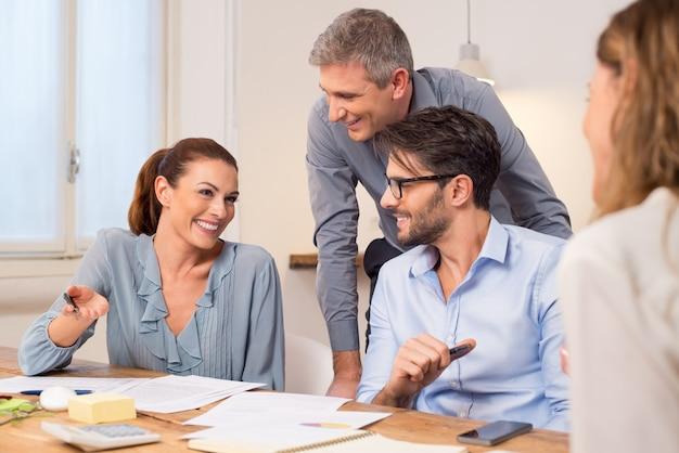 Tevreden ondernemers tijdens een vergadering. glimlachend zakelijk teamwerk na het krijgen van een deal. groep gelukkige jonge zakenmensen in een bijeenkomst op kantoor met manager.