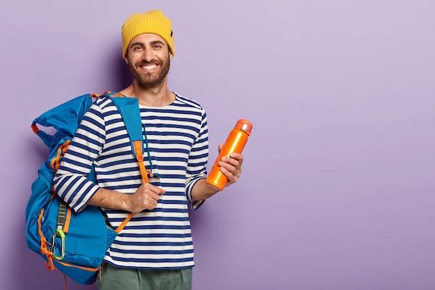 Tevreden ongeschoren man houdt thermosfles en grote rugzak vast, klaar voor avontuurlijke reis, lacht graag, gekleed in vrijetijdskleding, geniet van warme drank geïsoleerd op paarse achtergrond vrije ruimte voor uw advertentie