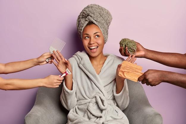 Tevreden ontspannen vrouw draagt een badjas en een gewikkelde handdoek op het hoofd