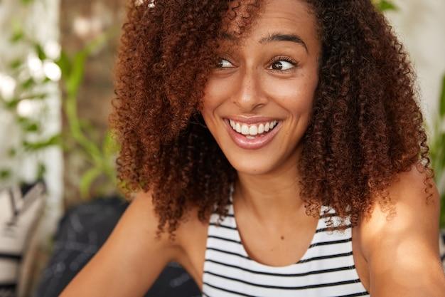 Tevreden opgetogen afrikaanse amerikaanse vrouw heeft knapperig haar