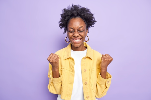 Tevreden opgewonden jonge vrouw met donkere huid heft gebalde vuisten op om iets te vieren