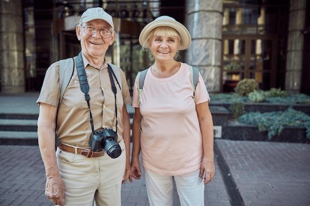 Tevreden oude man met een digitale camera en zijn vrolijke vrouw die buiten staat